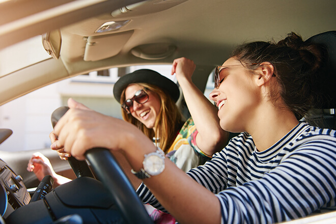 Two female teenage friends driving while listening to music and singing.