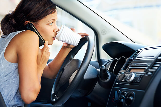 Woman multi-tasking, talking on phone and drinking coffee, while driving. Common car accident causes and how to prevent them.