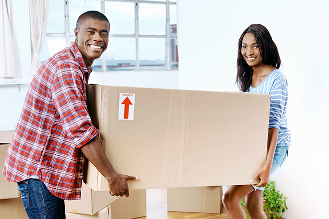 Man and woman couple moving a large box together.