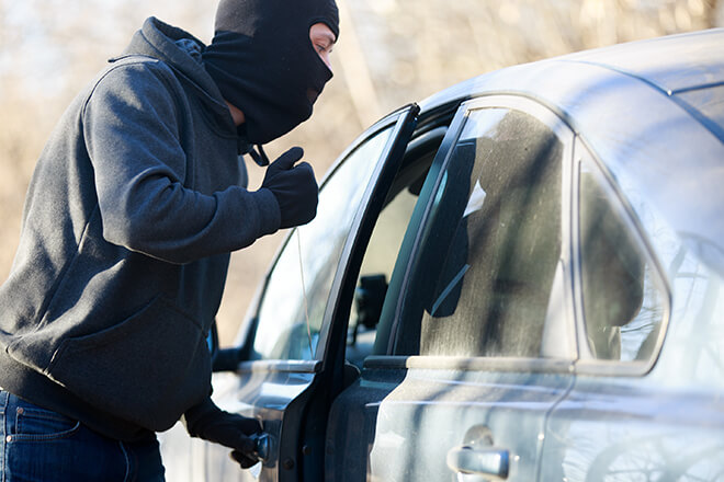 Burglar in mask breaking into a car.