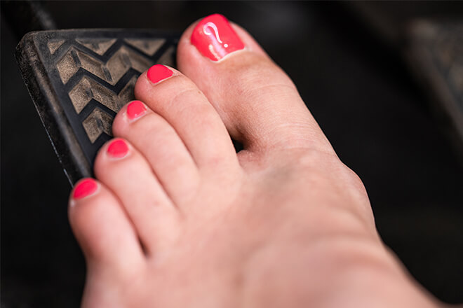 Bare foot with painted toenails on the pedal of car.