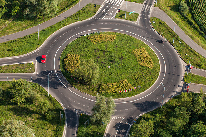aerial view of a roundabout or traffic circle with red car driving around it.