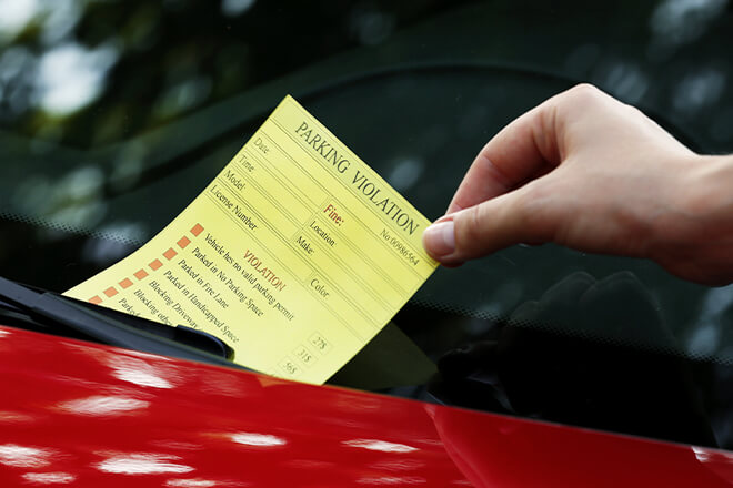 A yellow ticket on the windshield of a red car.