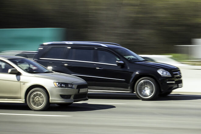 Black car speeds right past a silver car.