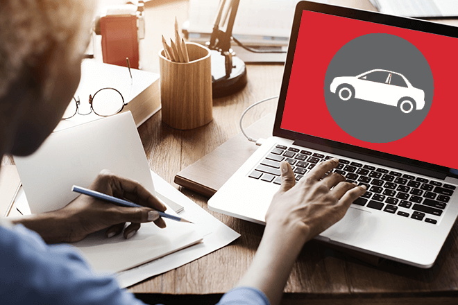 Woman sitting at laptop with car graphic icon on screen.