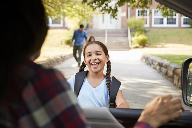 Student with pigtails running toward her mom's car in the school pickup line
