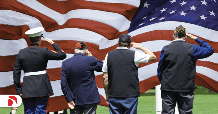 A group of military veterans saluting the flag