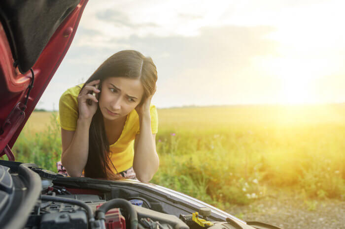 Girl in yellow shirt calling roadside assistance with her hood opened to her engine.