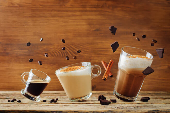 Espresso, cappuccino, and mocha coffee with their ingredients of cinnamon, chocolate, and coffee beans floating above on a wood table.