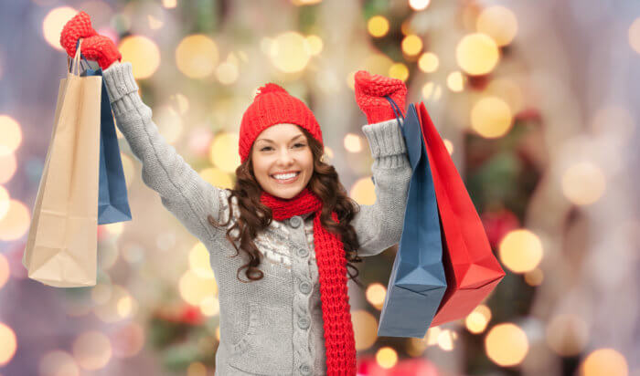 Happy young woman in winter clothes holding shopping bags up with a Christmas tree behind her