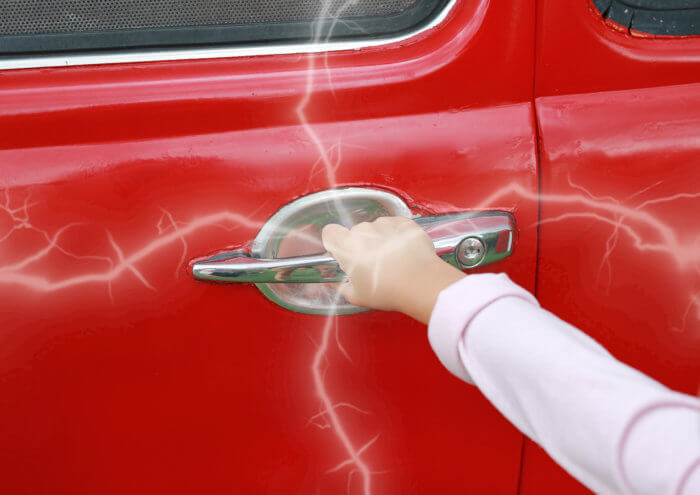 Childs hand grabbing a car door and getting shocked by static electricity from the red car.