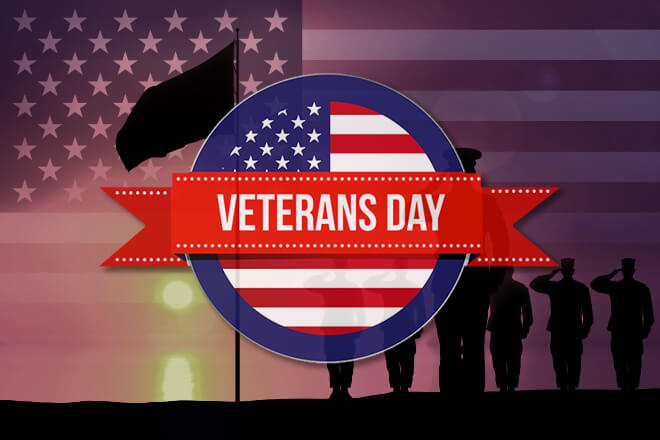 "Badge displaying ""Veteran's Day"" with soldiers saluting and the flag flying overhead while an American flag encompasses the entire background."