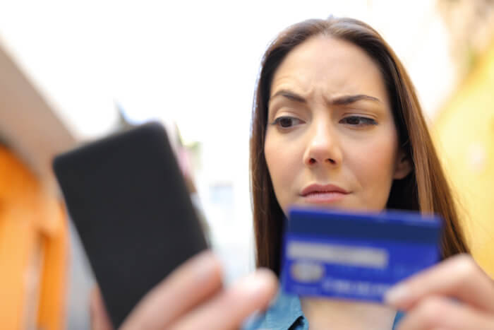 Woman looks skeptical with raised eyebrow while holding credit card and phone