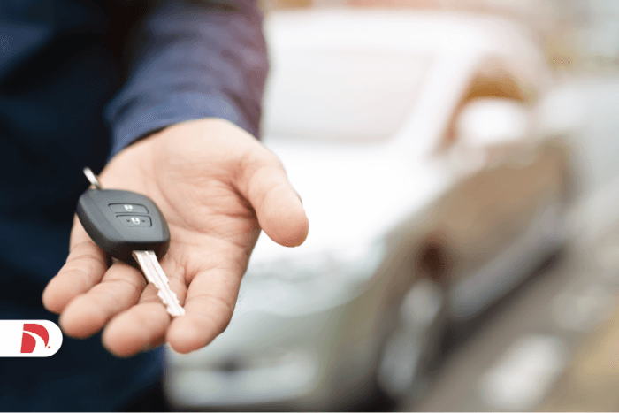 A man holding a car key in his left hand