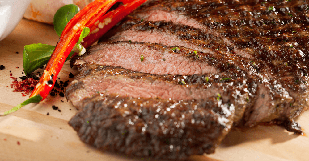 Juicy marinated steak, cooked medium, sliced on a cutting board