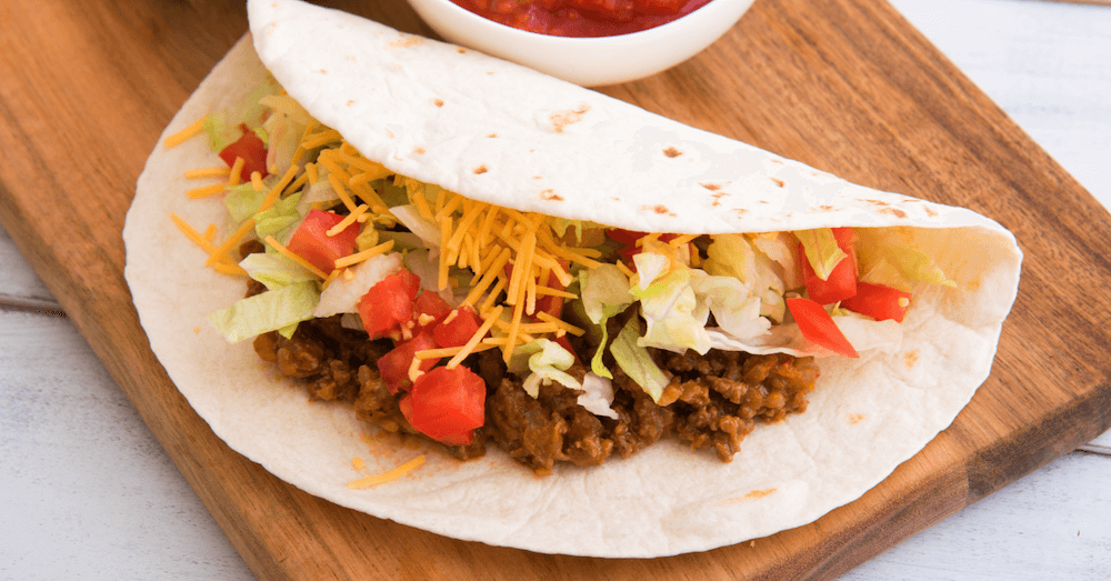 Soft shell taco filled with ground beef, diced tomatoes, shredded lettuce, and cheese