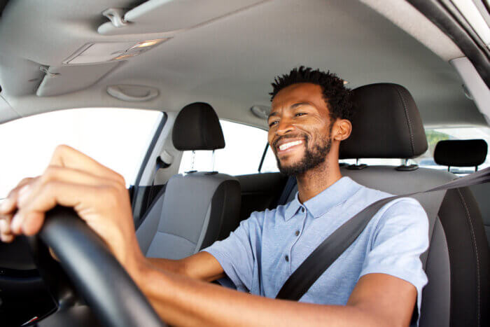 Close up of a smiling Black man driving a car how to prevent road rage