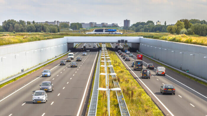 Why do some countries drive on the left? Afternoon commuting traffic on a4 motorway near The Hague Randstad area. Highway crossing aquaduct tunnel with urban area of Rotterdam in backdrop, Netherlands.