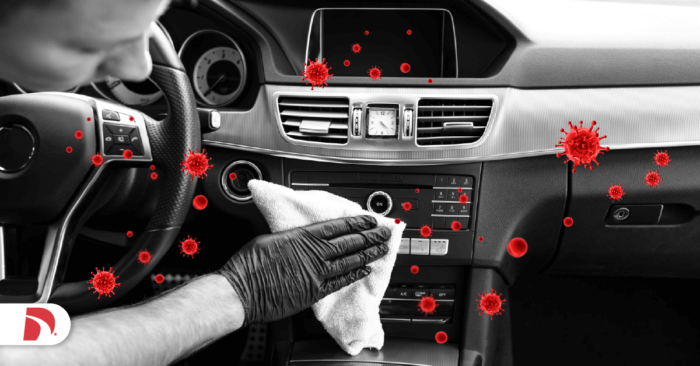 black and white car dashboard with a hand in a rubber glove disinfecting radio controls is your car making you sick
