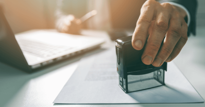 What is a notary hand notarizing a document with a stamp